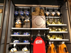 A newly renovated store awaits shoppers complete with a row of multiple check out registers for improved guest service. Greedo mugs have been added to the Star Wars themed apparel, accessories, and other merchandise. New shelving and display decor is present, along with an additional station now available to assist guests build ing their own light sabers. Disney's Hollywood Studios. Photo by John Capos