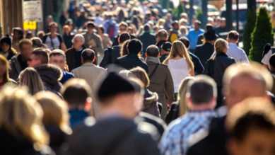 A image of a large body of people walking past each other in a city.