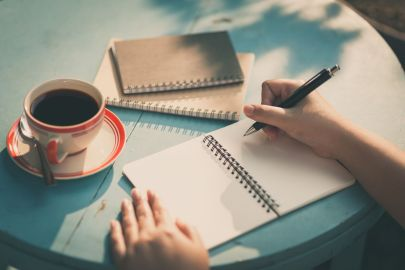 a person writing in a journal with a cup of coffee