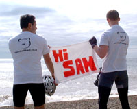 Hi Sam message on the beach showing t-shirts from the back