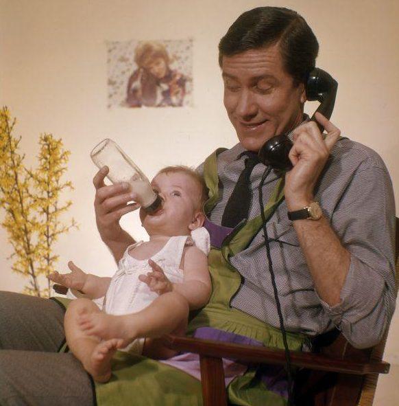 Telefonerende vader met huishoudschort geeft baby de fles. [1961].