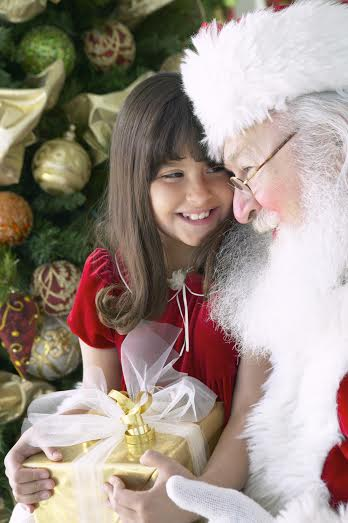 Santa Claus Sitting With a Young Girl by a Christmas Tree