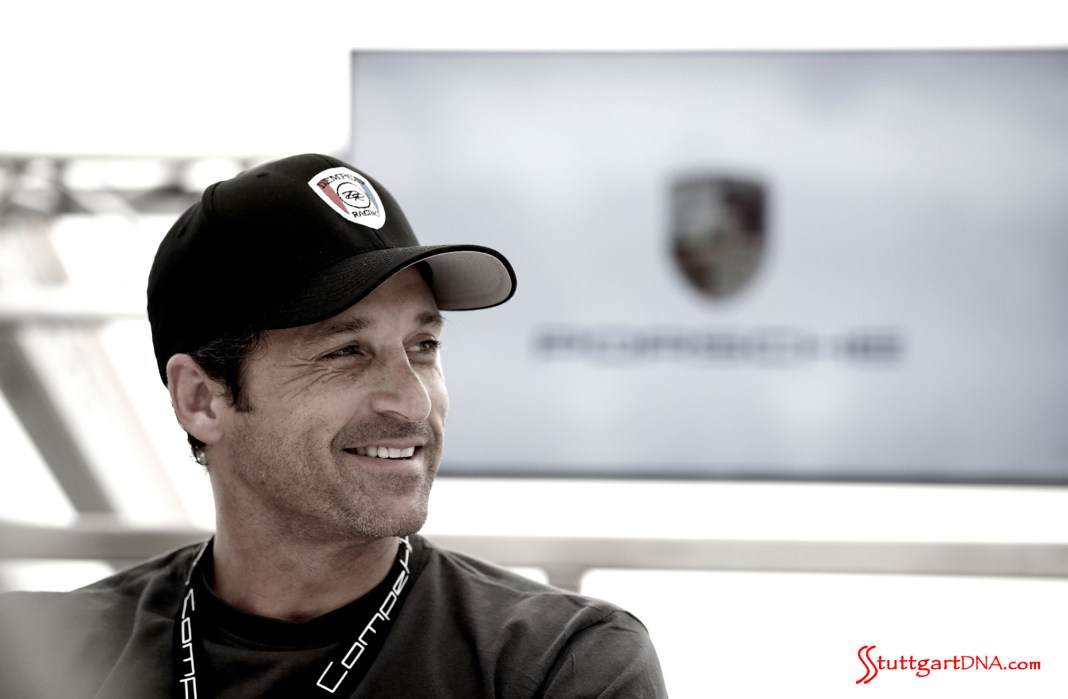 Patrick Dempsey pilots Porsche in 2015 WEC: Patrick Dempsey seen here in a right-side portrait, with Porsche flag in b.g. He signs with Porsche again to contest the 2015 FIA WEC and Le Mans. Source: Porsche AG