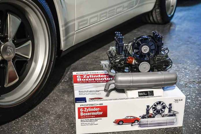 Franzis' Porsche Flat-Six Engine Scale Model Kit: Seen here is the 911 model engine on its packing box, beside a Fuchs wheel and a white 911. Credit: Flat Six Fanatics
