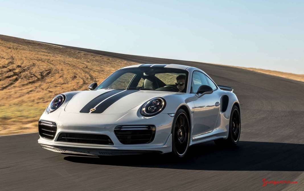 January 2018 USA Porsche sales: Seen here is a white 911 Turbo S Exclusive, from its left-front corner, coming out of a right turn on a racetrack. Source: Porsche AG
