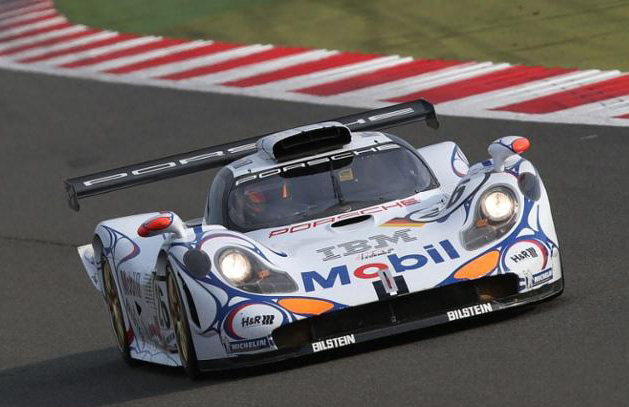 996-gen Porsche 911 Buyer Guide: Seen here is the Porsche 911 GT1-1998 at speed on track at the 2014 Silverstone Classic. The 911 GT1's awesomely crocodilian headlights are progenitors to the subsequent headlights of the early 996-gen Porsche 911 Carrera and the 986-gen Porsche Boxster. Credit: Porsche AG