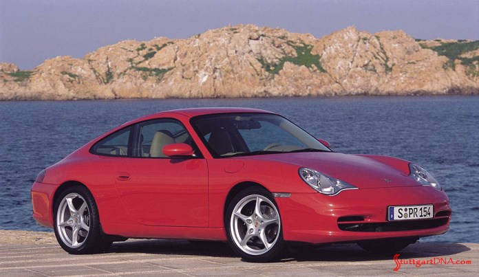 996-gen Porsche 911 Buyer Guide: Pictured here is a gleaming 996-gen Porsche 911 Carrera 4 red coupe, seen from its right-front corner, poised beside the shore. Credit: Porsche AG