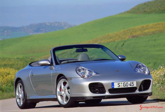 996-gen Porsche 911 Buyer Guide: A 996 Carrera 4S Arctic Silver Cabriolet, from its right-front view, is depicted here at rest on a serene country road among grass-covered hills. Credit: Porsche AG