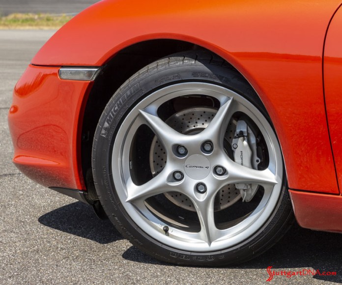 996-gen Porsche 911 Buyer Guide: Pictured here is a tight shot of a 996 left-front Carrera wheel and its silver caliper, which distinguishes the C4 from the rear-wheel-drive 996. Credit: Porsche AG