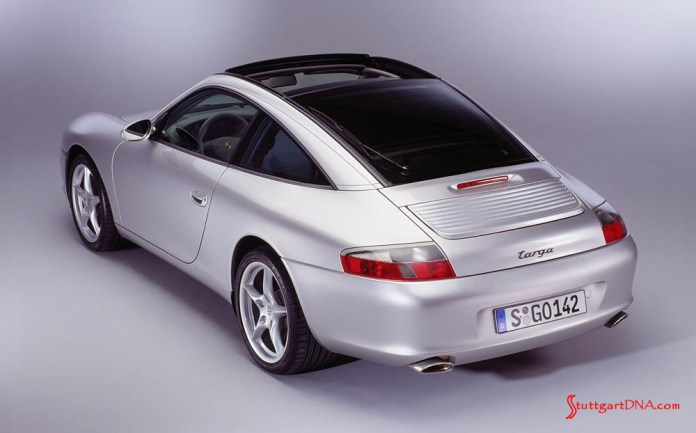 996-gen Porsche 911 Buyer Guide: This is a brochure photograph of an at-rest 996 silver Targa, shot from a high left-rear angle in a studio. Credit: Porsche AG