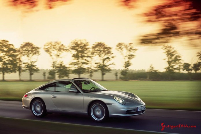 996-gen Porsche 911 Buyer Guide: Depicted in this photo is a 996 silver Targa, viewed from its right front, as it smoothly tools down a country road. Credit: Porsche AG