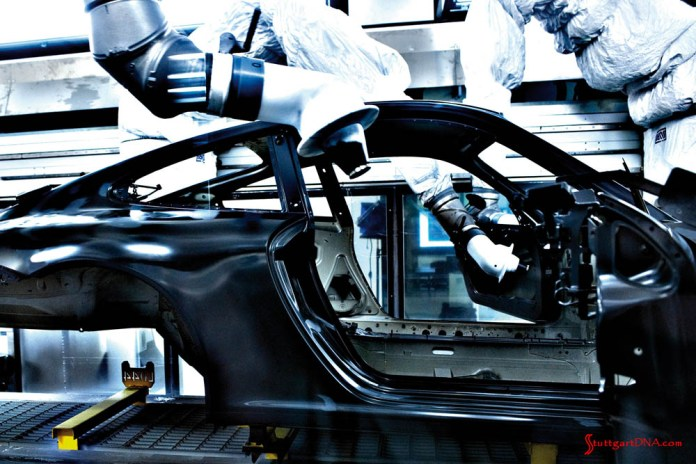 996-gen Porsche 911 Buyer Guide: Seen in this factory photo are paint atomizer robots hovering over a 911 body shell, which is about to be spray-painted. Credit: Porsche AG