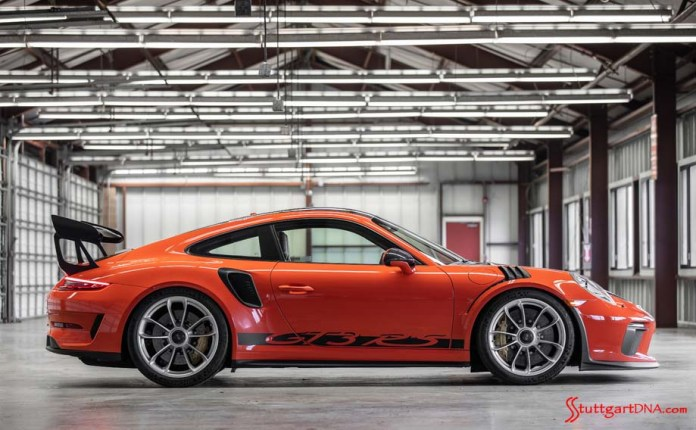 991.2-gen Porsche 911 Buyer Guide: Depicted here is a Lava Orange Porsche 911 GT3 RS, seen from its right side inside a track garage setting. Credit: Porsche AG