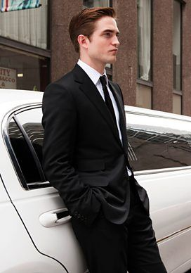 Robert Pattinson as Eric Packer in a tailored, sexy suite outside his limo. Cosmopolis, David Cronenberg (2012)