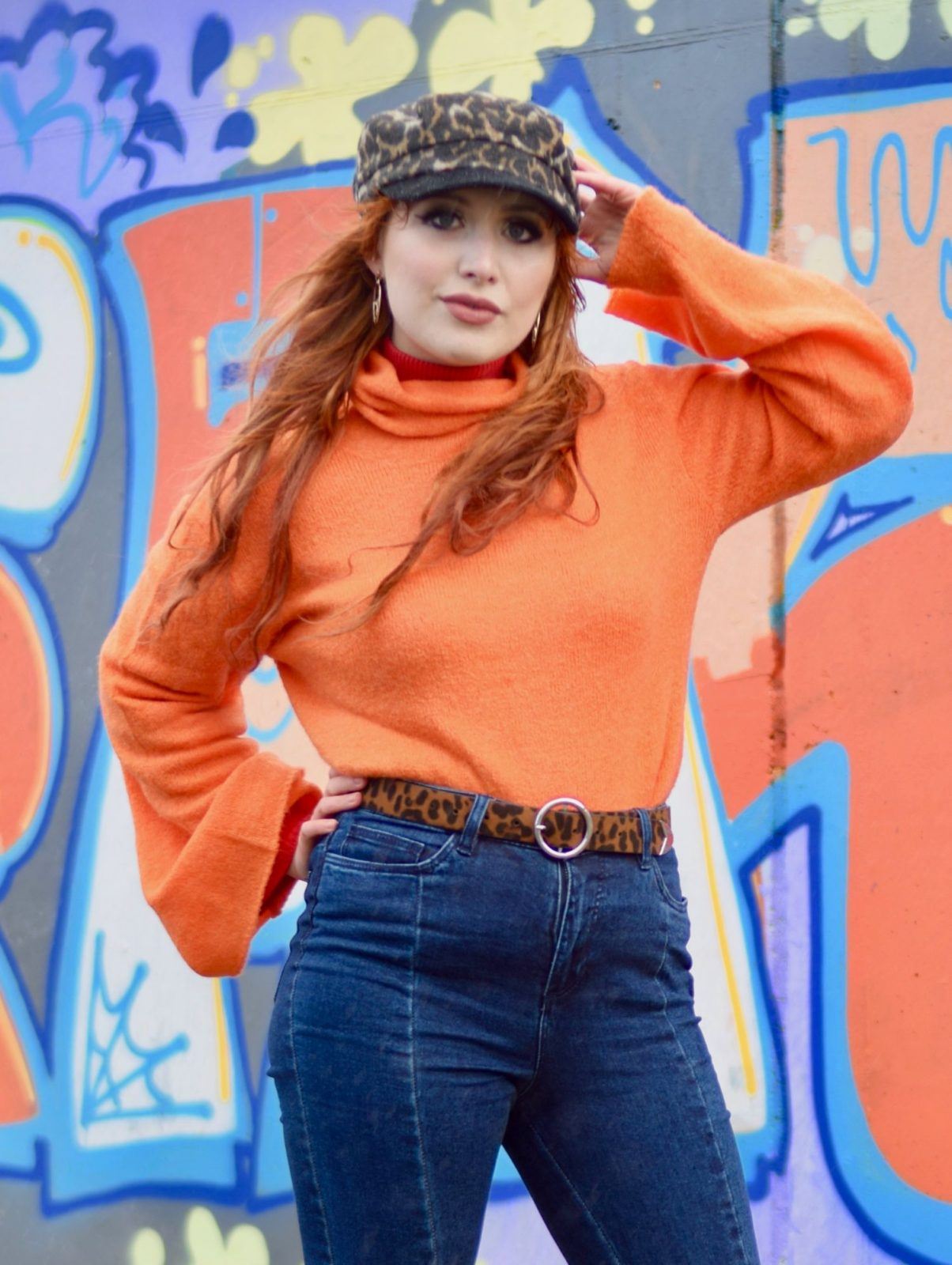 Blogger Twenty-Something City wearing orange flute sleeve jumper and leopard print bakerboy hat