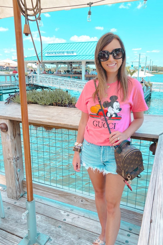 pink mickey mouse gucci disney tee with agolde shorts and louis vuitton palm springs mini