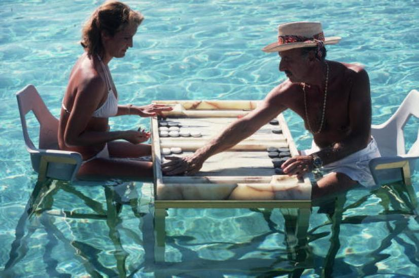 Carmen Alvarez enjoying a game of backgammon with Frank 'Brandy' Brandstetter in a swimming pool at Acapulco.   (Photo by Slim Aarons/Getty Images)