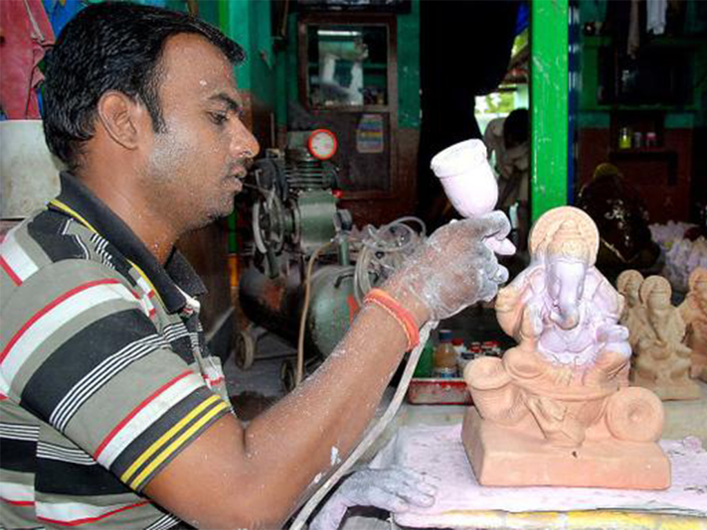 Artist sculpting Ganesha