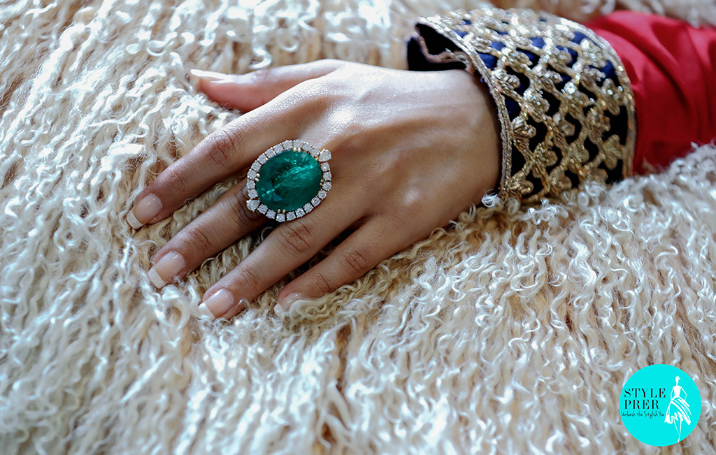 An Emerald And Diamond Cocktail Ring Worn With An Ethnic Red And Blue Lehenga