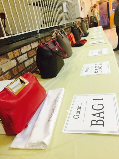 Bags from Michael Kors, Coach, Dooney & Bourke and Kate Spade lined the prize table. Bag 1 was a red Michael Kors clutch valued at $198.