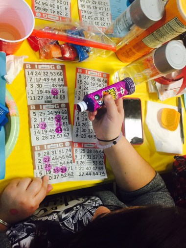 A player marks her sheet according to the specific pattern chosen for the game. Her purple dauber marks how close she is to winning.