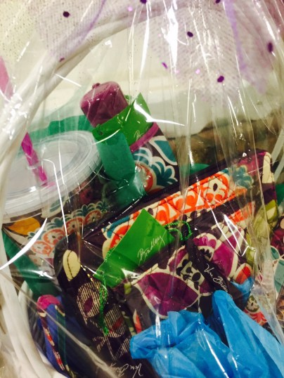 A raffle basket includes mini Vera Bradley bags, a cup and an umbrella in one matching pattern.