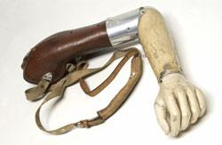 Artificial left arm with shoulder straps. Made with leather and aluminium by W R Grossmith.