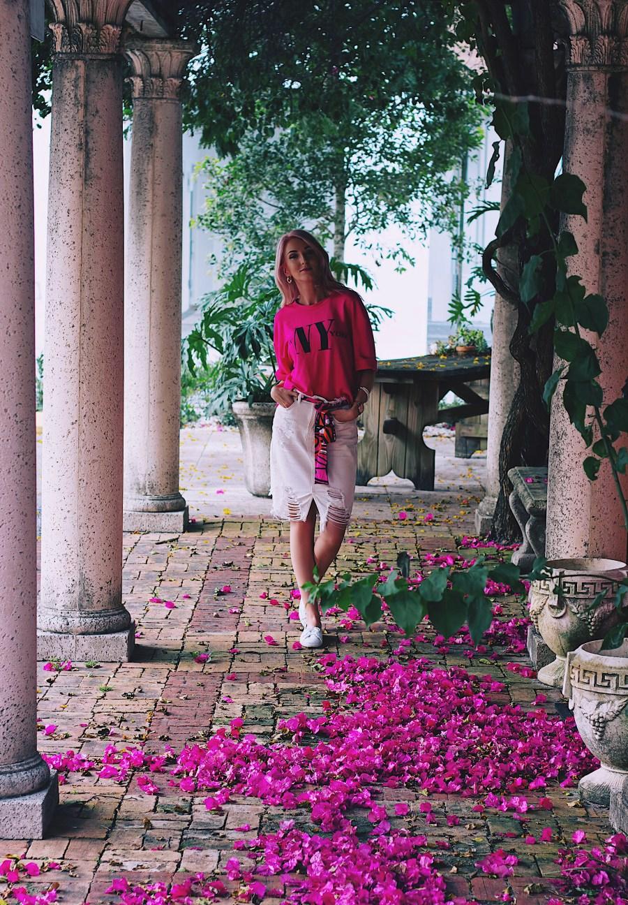 Fuchisa pink cropped sweatshirt, white distressed denim skirt and white sneakers