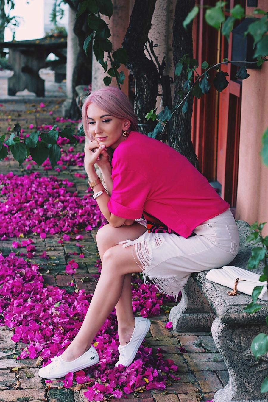 Fuchsia pink cropped sweatshirt, white distressed denim skirt and white sneakers