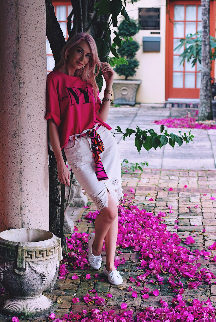 Pink cropped sweatshirt, white distressed denim skirt and white sneakers