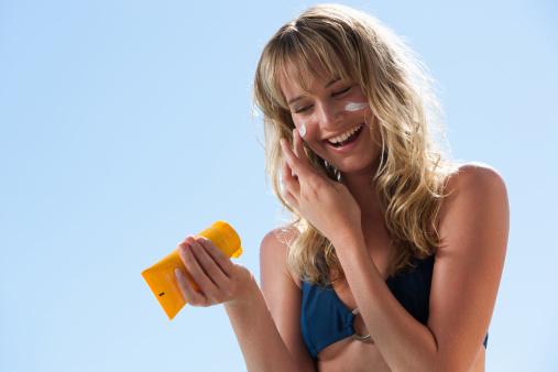 types of sunscreen // Woman in bikini with sunblock