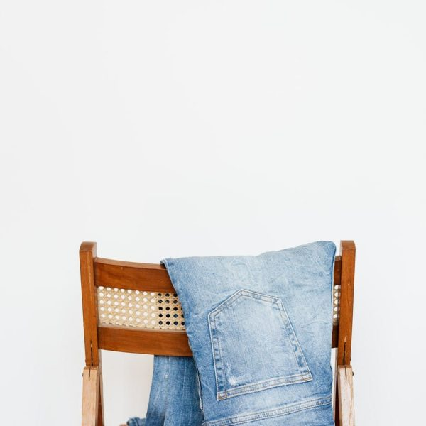 stylish jeans hung on wooden chair