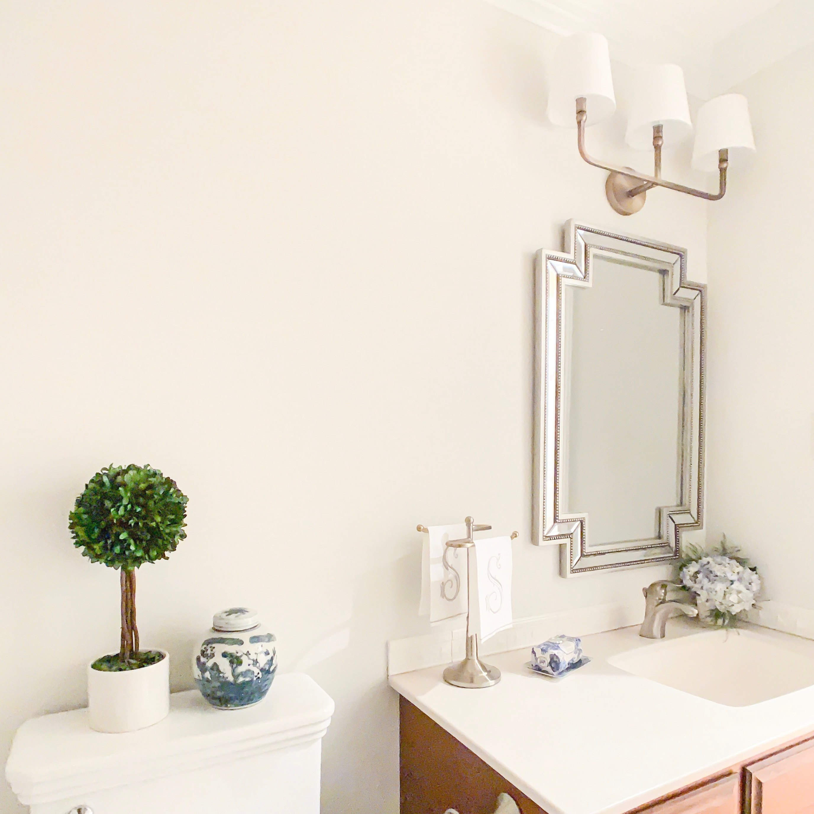 Styling Gypsy Interior Design traditional powder room featuring geometric beaded mirror, aged brass triple sconce, blue and white ginger jar, preserved boxwood topiary and other bathroom decor. Walls painted Benjamin Moore Classic Gray