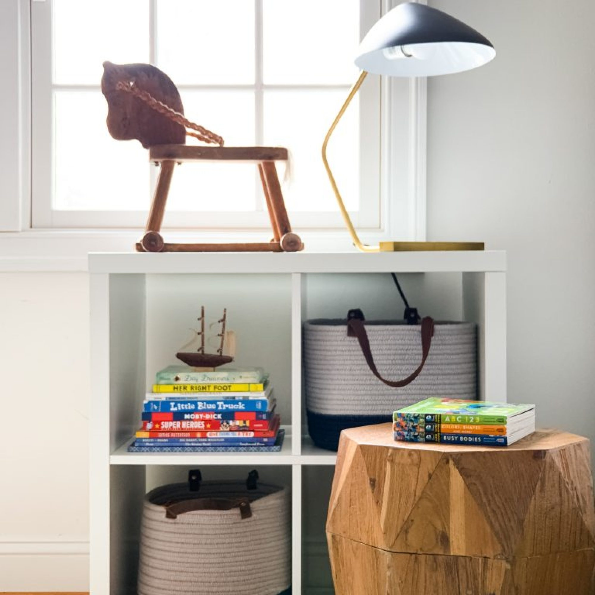 Styling Gypsy Interior Design | Classically Cool Boys Room reveal.  Shelf vignette featuring ikea kallax shelves, children's books, braided wool storage baskets, vintage rocking horse, midcentury lamp and geometric wood stool  #boysroom #boysroomideas #boysroominspiration #starwarsbedroom #boysroomdecor #kidsroom #shelfie