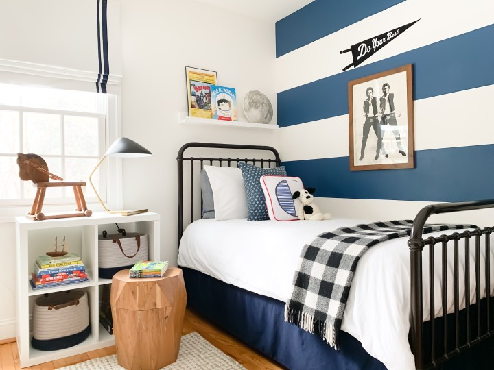 Styling Gypsy Interior Design | Classically Cool Boys Room reveal featuring a blue and white striped accent wall, iron bed, mid-century table lamp, geometric wood stool, beige wool rug, white bedding, newport cross pillow, letter block pillow, black plaid throw blanket, star wars art prints, navy blue storage baskets and ikea kallax shelves #boysroom #boysroomideas #boysroominspiration #starwarsbedroom #boysroomdecor #kidsroom