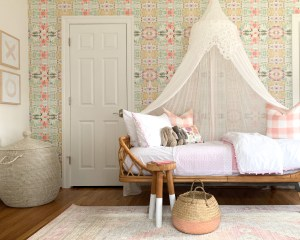 Styling Gypsy Interior Design | Eclectic Pink Girls Room mini reveal featuring graphic pink wallpaper with purple and aqua accents, anthropologie rattan daybed, pink geometric rug, serena and lily wood dipped stool, seagrass storage baskets, pink and white bedding, blush pink buffalo check pillow, pottery barn kids bed canopy, pink dipped seagrass basket, pink xo art prints, pom pom bedding #girlsroom #pinkgirlsroom #girlsroominspiration #pinkbohemianbedroom #biggirlroom