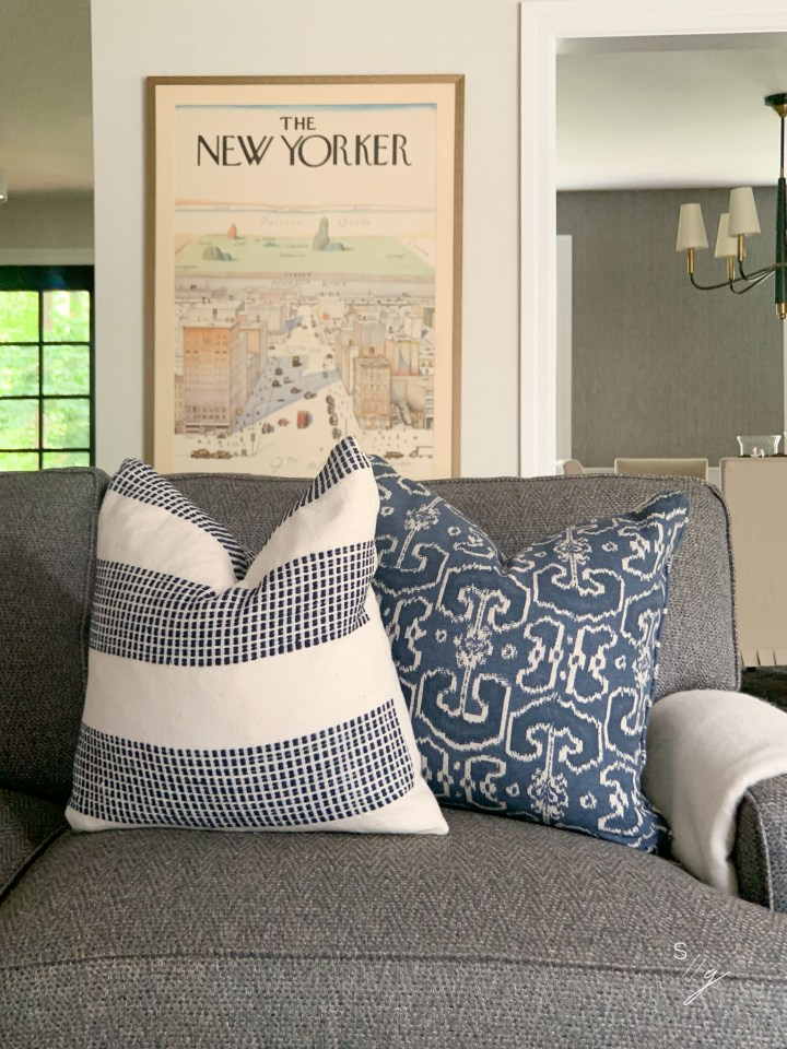 Styling Gypsy Interior Design cozy and welcoming den design featuring neutral paint, tailored blue herringbone sofa, indigo ikat pillow, blue and white stripe pillow, poster art and clean and modern dining room chandelier.