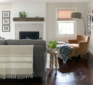 Styling Gypsy Interior Design cozy and welcoming den design featuring neutral paint, tailored blue herringbone sofa, camel velvet curved armchair, ottoman, turned leg wood side table, arc floor lamp, linen shades, shiplap fireplace with rustic wood mantel.