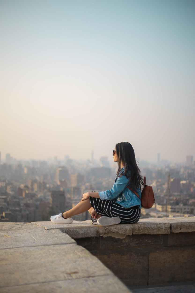woman sitting on top of building s edge