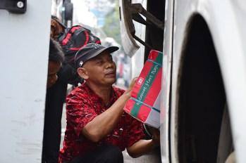 Seorang petugas sedang memasukan barang bawaan penumpang. (Foto: Fajrul Islam/SuaraJakarta)