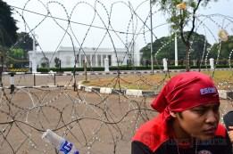Salah seorang buruh beristirahat membelakangi Istana Negara dan kawat berduri. (Foto: Fajrul Islam/SJ)