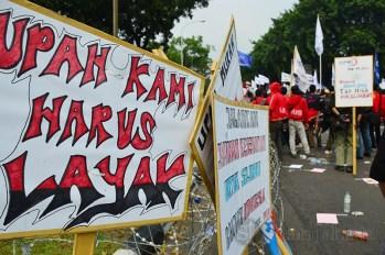 """Poster bertuliskan """"upah kami harus layak"""" dipasang di kawat berduri. (Foto: Fajrul Islam/SJ)"""