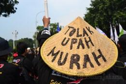 Salah seorang buruh memakai topi capi yang bertuliskan tolak upah murah. (Foto: Fajrul Islam/SJ)