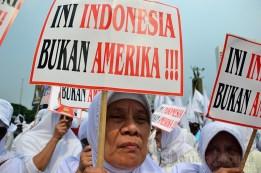 """Seorang ibu membawa poster """"Ini Indonesia, Bukan Amerika' sebagai bentuk penolakan terhadap Miss World 2013. (Foto: Fajrul Islam/SJ)"""