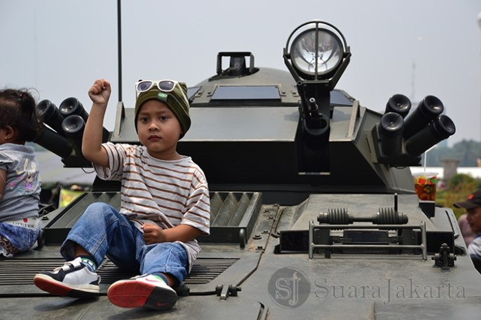 Seorang anak sedang berpose di depan mobil tank milik TNI. (Foto: Fajrul Islam)