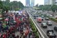 Buruh berunjukrasa di depan Gedung DPR-MPR dan bersebelahan dengan hilir mudik kendaraan di jalan tol dalam kota. (Foto: Fajrul Islam)