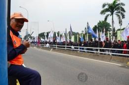 Salah seorang petugas jasa marga memantau aksi unjukrasa di depan pintu tol dalam kota. (Foto: Fajrul Islam)