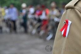Salah seorang anggota komunitas sepeda ontel mengenakan pita merah putih pada peringatan Hari Pahlawan di Makan Pahlawan, Tangerang Selatan. (Foto: Fajrul Islam/SuaraJakarta)