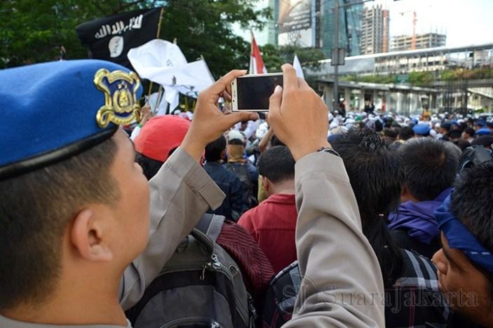 Seorang polisi sedang memotret demo yang dilakukan Masa FPI dan HTI di depan Kedubes Australia (22/11) Kuningan, Jakarta. (Foto: Fajrul Islam)