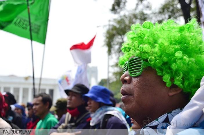 Seorang guru honorer memakai wig dan kaca mata hijau pada peringatan May Day di depan Istana Merdeka, Jakarta (1/5). (Foto: Fajrul Islam)